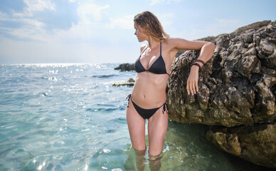 fit woman in posing on beach.  woman posing by sea  at sunset time. Woman with sport body. Weight loss by summer, motivation. Fit body, abs.