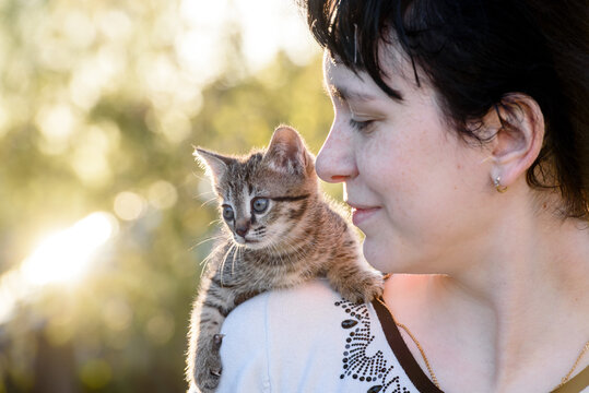 A small kitten sitting on the shoulder of a girl on a walk.