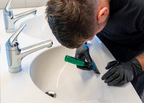 professional cleaner removing lime scale from a ceramic bathroom sink with a diamond blade scraper