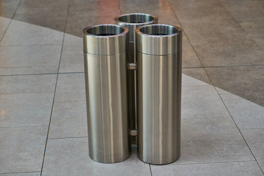 Stainless steel trash can for sorting garbage. Three containers of gray and steel color. The purity of the world. Taking care of the order.