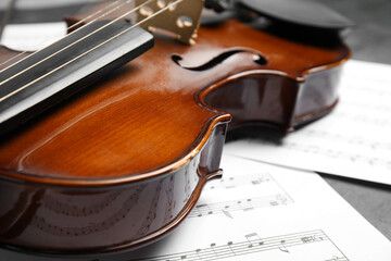 Beautiful violin and note sheets on table, closeup