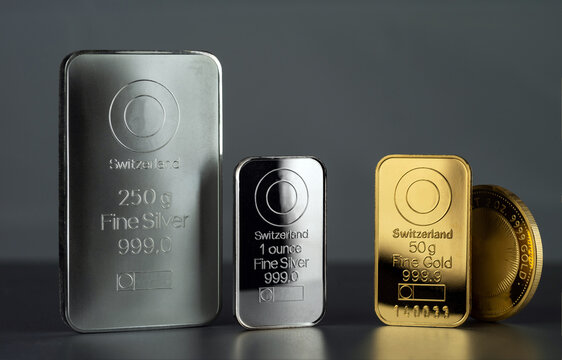 Silver and gold bars and coin on a dark background.