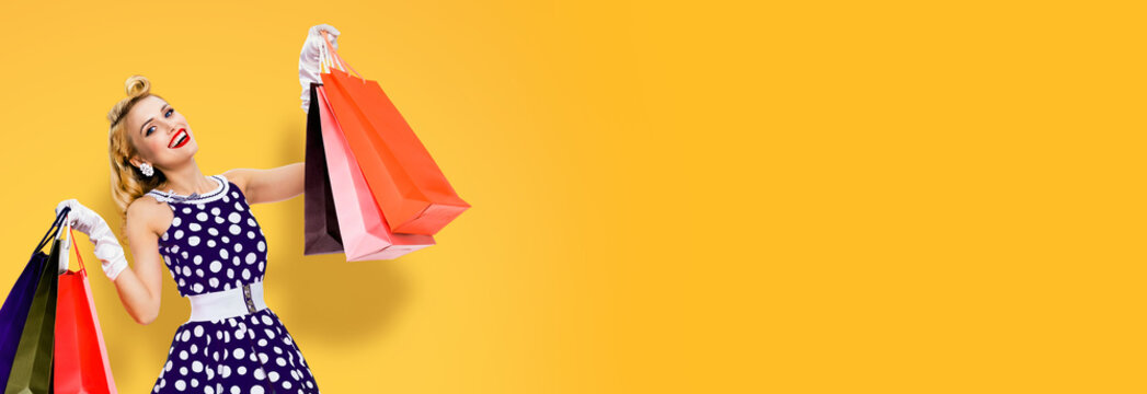 Woman in pinup style dress holding, showing or giving many shopping bags, over orange yellow color background with copy space empty area. Big sales or consumer bank credit concept picture.