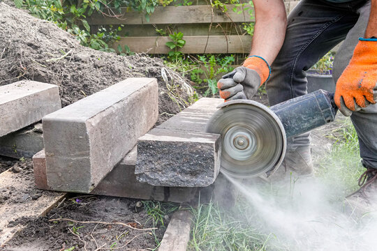 A skilled worker using an angle grinder to cut large stone