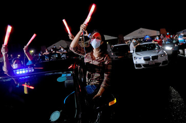 Fans wearing protective masks dance inside a car during the first drive-in concert, in Colombo