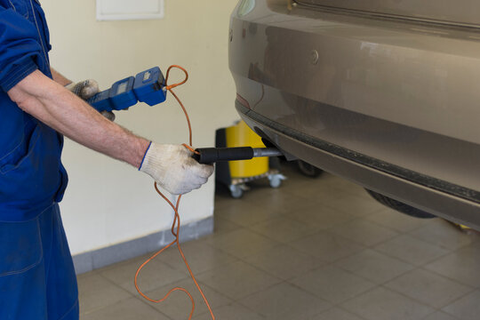 Car repair at a service station. A professional mechanic measures the exhaust of a car. Car exhaust control.