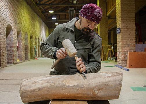 the artist crafts wood in studio