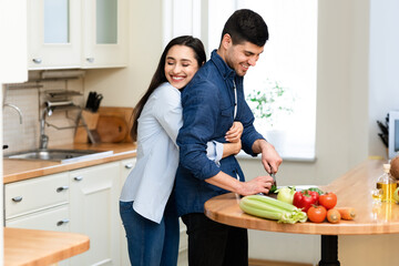 Lovely couple preparing dinner cutting vegetables at home