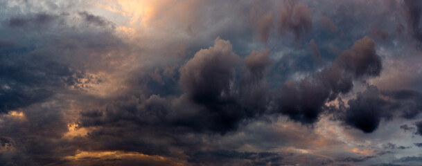 wide panoramic view of the dramatic sunset sky with dark cumulus clouds and natural purple-orange illumination from the evening dawn. Artistic backdrop for atmospheric design or decoration Fotobehang
