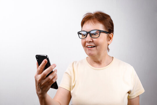 Senior woman in glasses looks at the phone on a white background in a light T-shirt. place for text, isolated