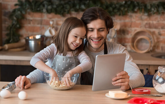 Little Girl And Her Dad Checking Recipe On Digital Tablet While Baking