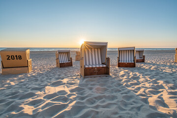 Wall Mural - Roofed wicker beach chairs at the North Sea coast on Sylt, Germany