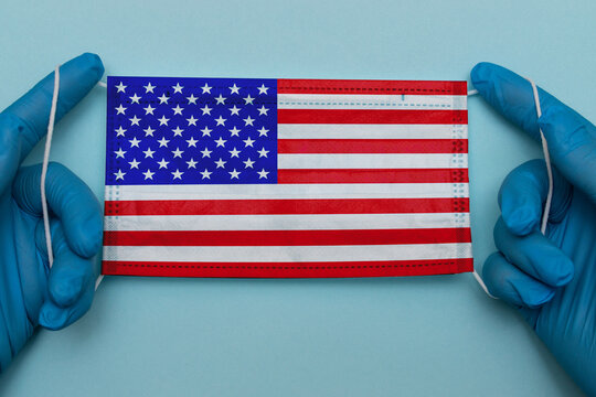 American flag on a medical mask in the hands of a doctor on a blue background.Independence Day Of USA 2020 during coronavirus Covid-19 pandemic