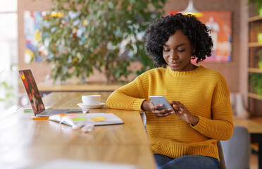African girl using smartphone, working online at cafe