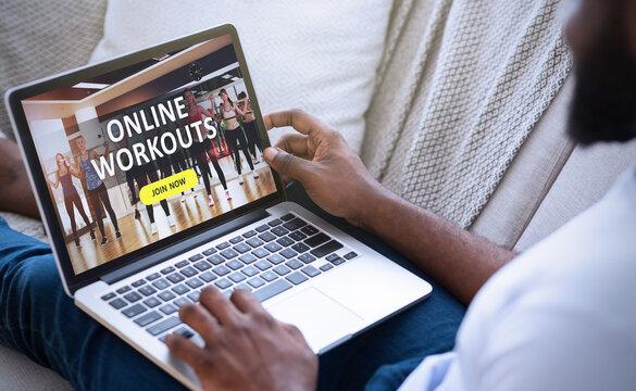 Black man watching sport training online on laptop