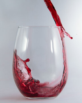 Red wine pouring and spilling over the edge of a stemless glass