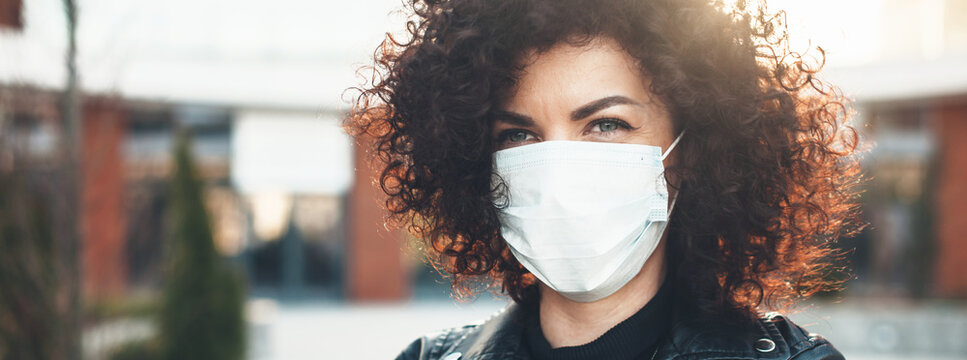 Close up photo of a curly haired woman wearing a protective mask outside and looking at the camera