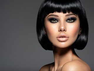 Beautiful fashion woman with a bob hairstyle looks to the camera.  Сloseup face of a sexy fashion model with black gloss make-up,  Attractive white girl with black eye-makeup.  Art.