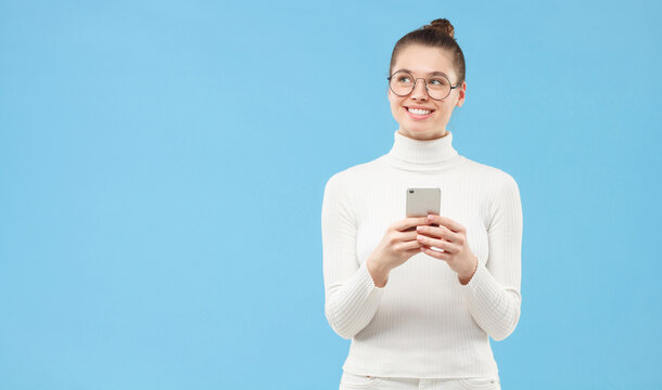 Young smiling woman in white sweater and eyeglasses, standing with cellphone in hands, looking aside thinking of something pleasant, isolated on blue background with copy space