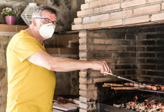 Man making a barbecue with a mask after the coronavirus