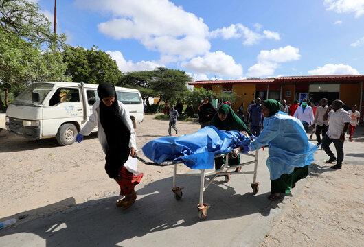 Paramedics and civilians at Madina hospital assist an injured man after a minibus struck a roadside bomb at Hawa Abdi village, northwest of Mogadishu