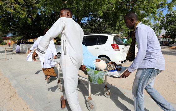 A paramedic and civilians at the Madina hospital assist an injured woman after a minibus struck a roadside bomb at Hawa Abdi village, northwest of Mogadishu
