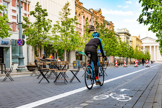 Rider cycling on the road bike in Vilnius city center reopening with open air restaurant and bar during Covid or Coronavirus emergency, sustainable transport concept