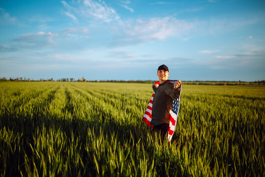 Young man wearing green shirt and cap stands wrapped in the american flag at the green wheat field. Patriotic boy celebrates usa independence day on the 4th of July with a national flag in his hands.
