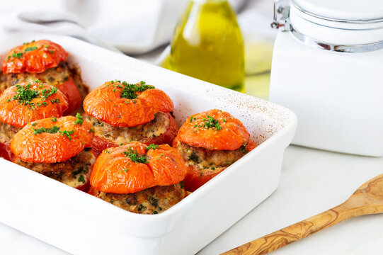 French stuffed tomatoes with meat, bread crumbs, and herbs in a white ceramic dish, aside white napkin, a bottle of olive oil and an olive wood serving spoon.