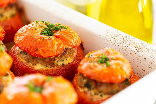 Close-up on French stuffed tomatoes with meat, bread crumbs, and herbs in a white ceramic dish, aside a bottle of olive oil.