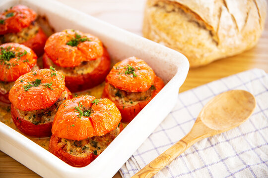 Mediterranean stuffed tomatoes with meat, bread crumbs, and herbs in a white oven dish, aside a kitchen towel, a bread loaf and a wooden serving spoon on an oak wood table.