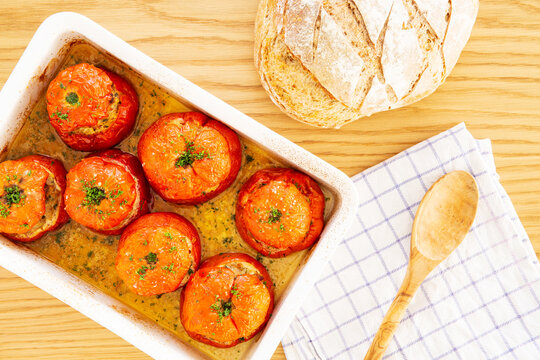 Mediterranean stuffed tomatoes with meat, bread crumbs, and herbs in a white oven dish, aside a kitchen towel,, a bread loaf and a wooden serving spoon on an oak wood table. Flat Lay, top view.