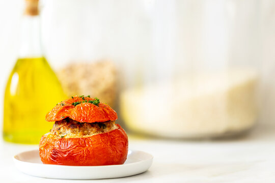 Mediterranean stuffed tomatoes with meat, bread crumbs, and herbs in a small white plate with an olive oil bottle and some rice jars in the background on a marble kitchen table.