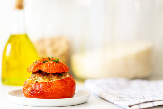 Mediterranean stuffed tomatoes with meat, bread crumbs, and herbs in a small white plate with a kitchen towel, an olive oil bottle and some rice jars in the background on a marble kitchen table.