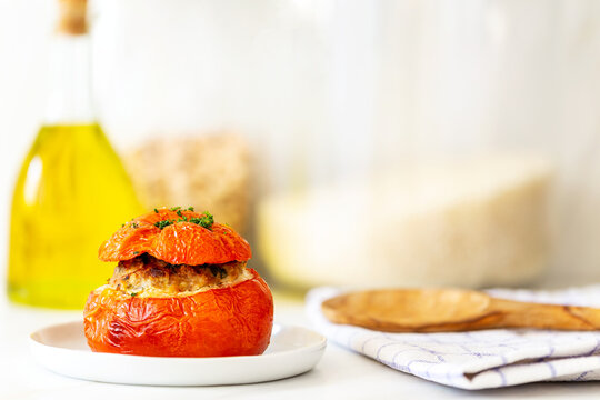 Mediterranean stuffed tomatoes with meat, bread crumbs, and herbs in a small white plate with a kitchen towel, a serving spoon, an olive oil bottle and some rice jars in the background on a marble kit