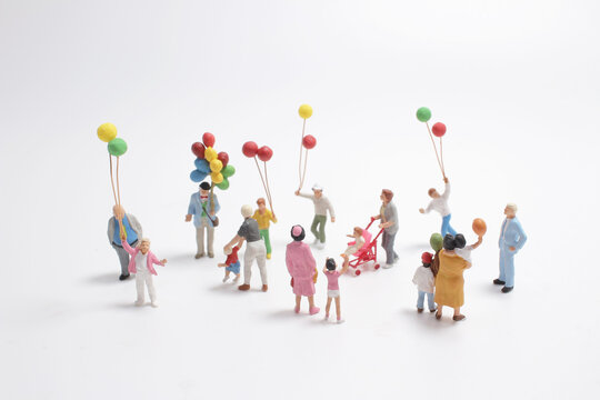 a mini people with family holding balloon on the board