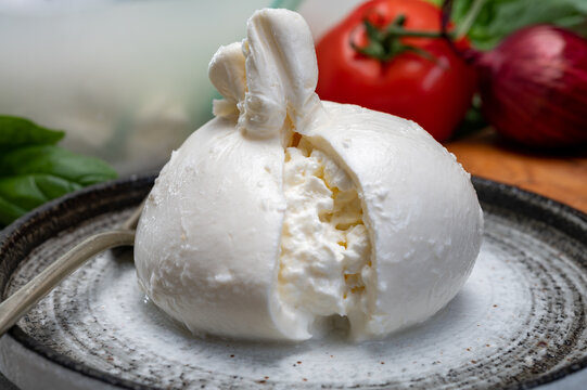 Eating of fresh handmade soft Italian cheese from Puglia, white balls of burrata or burratina cheese made from mozzarella and cream filling