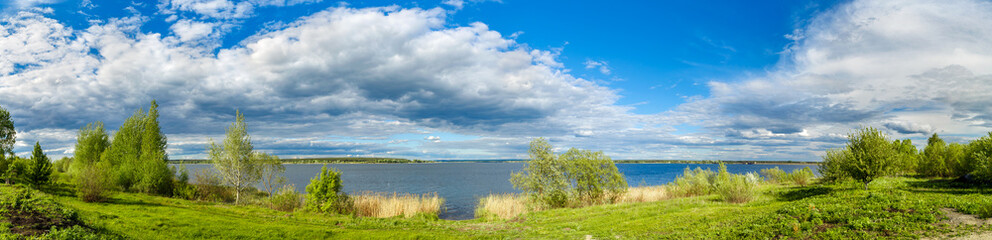 Fototapete - Summer landscape with lake, blue sky and clouds. Nature wilderness. Countryside outdoors, relaxation, space scenic. Beautiful pond, forest, green meadow with reflection in water. Panoramic views.