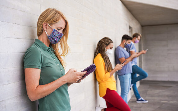 Young people wearing face safety masks using smart mobile phones while keeping social distancing during coronavirus time - Technology and covid-19 spread prevention concept - Focus on blond girl hand