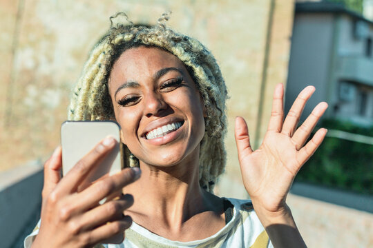 Yound african woman with blond dreadlocks doing video call with smart mobile phone - Trendy person having fun with technology trends - Tech, lifestyle and social media concept