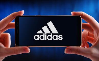 Hands holding smartphone displaying logo of Adidas
