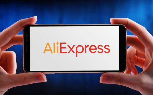 Hands holding smartphone displaying logo of AliExpress