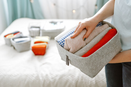 Woman organizing clothes in bedroom wardrobe, putting laundry in boxes, baskets into shelves. Concept of minimalism lifestyle and japanese t-shirt folding system. Minimalist closet