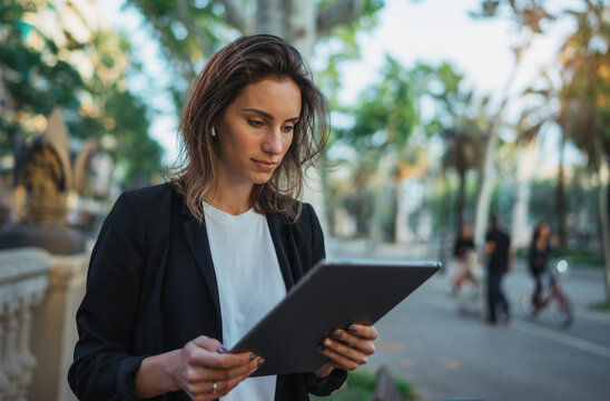 Young businesswoman with tablet walking in barcelona city park. Young business woman using modern laptop outdoors, professional female  banker or lawyer searching information in internet via pc