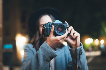 Fotomurales - Photographer tourist girl with retro camera take photo on background bokeh light in evening city, Blogger photoshoot photo hobby