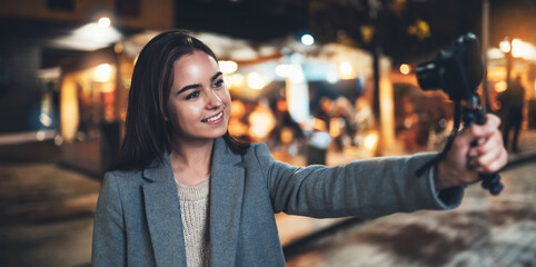 Fotomurales - Female vlogger recording with digital camera. Smiling woman taking selfie video on light night city. Traveler making video for her blog. Vlogger uses photo technology for shoot social media