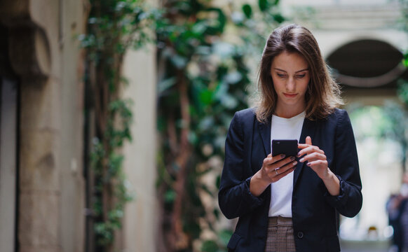 hipster girl reading text business message from her managers connected to public internet outdoors, beautiful professional woman chatting on cell smartphone while relaxing outdoors