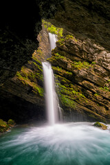 Wall Mural - idyllic waterfall in lush green spring foliage landscape in the Swiss Alps