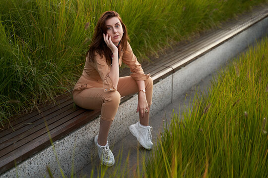 Young beautiful red haired gen z girl wearing slim fitted women beige khaki coverall overall denim jumpsuit or flight suit and white chunky platform sneakers sitting on a long park bench in high green