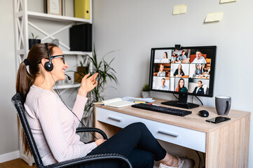 Young successful employee is have a meeting with her team using a headset, she is sitting relaxed and smiling, a middle side shot.